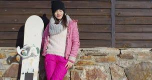 Donna con lo snowboard vicino alla parete della costruzione stock footage