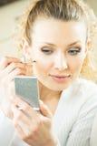Donna con lo specchio che fa volto Fotografia Stock