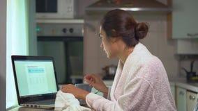 Donna con lo starnuto che scrive il prezzo a macchina delle pillole dentro alla tavola medica sul computer portatile video d archivio