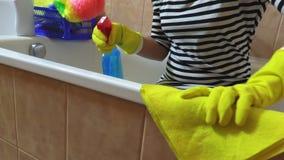 Donna con lo straccio giallo che lucida il bordo del bagno