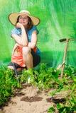 Donna con lo strumento di giardinaggio che funziona nella serra Fotografie Stock