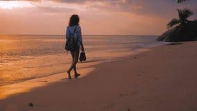 Donna con lo zaino che cammina sulla spiaggia, alla luce di tramonto, colpo dello steadicam archivi video
