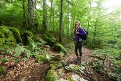 Donna con lo zaino che fa un'escursione nella foresta fotografia stock libera da diritti