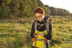 Donna con lo zaino che guarda alla bussola e che cerca il modo/g fotografia stock libera da diritti