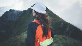 Donna con lo zaino ed il cappello bianco che viaggiano lungo le montagne nebbiose e nuvolose Fotografie Stock Libere da Diritti