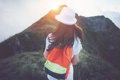 Donna con lo zaino ed il cappello bianco che viaggiano lungo le montagne nebbiose e nuvolose nel tramonto Fotografia Stock Libera da Diritti