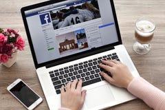 Donna con MacBook e iPhone con servizio Twi della rete sociale Immagine Stock