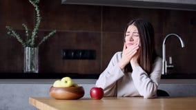 Donna con mal di denti che mangia mela rossa stock footage
