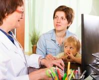 Donna con medico amichevole d'ascolto del pediatra del bambino Fotografia Stock