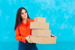 Donna con molti pacchetti delle scatole di cartone ricevuti da servizio di distribuzione Fotografia Stock
