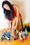Donna con molti pattini da scegliere da Fotografie Stock