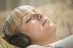 Donna con musica d'ascolto chiusa degli occhi tramite le cuffie Fotografia Stock