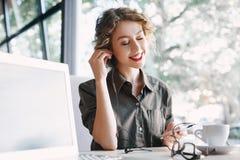 Donna con musica d'ascolto del telefono e del computer portatile in caffè Fotografie Stock Libere da Diritti