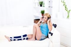 Donna con musica d'ascolto di ferita di piedino immagine stock