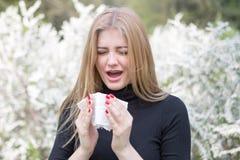 Donna con raffreddore da fieno davanti ai fiori bianchi Immagini Stock Libere da Diritti