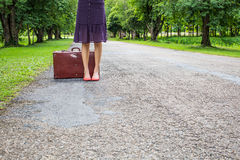 Donna con retro bagagli d'annata sulla via vuota Immagine Stock Libera da Diritti