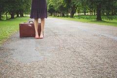 Donna con retro bagagli d'annata sulla via vuota Fotografia Stock