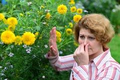 donna con con rinite vicino ai fiori gialli Fotografia Stock Libera da Diritti