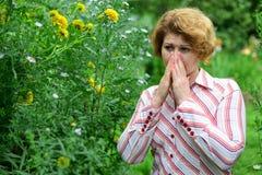 donna con con rinite vicino ai fiori gialli Fotografie Stock Libere da Diritti