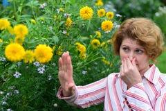 donna con con rinite vicino ai fiori gialli Immagine Stock