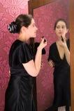 Donna con rossetto messo su trucco Immagine Stock