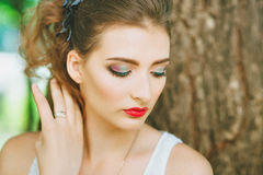 Donna con rossetto rosso e trucco colorato, ritratto in natura Guardando al lato I suoi occhi coperti Immagini Stock