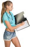 Donna con scrittura dello stetoscopio sulla lavagna per appunti in bianco Immagine Stock