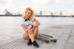 Donna con smartwatch sul suoi polso e longboard fotografie stock