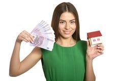 Donna con soldi e poca casa Immagini Stock Libere da Diritti