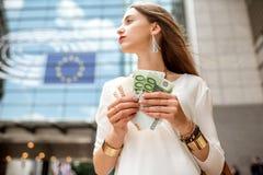 Donna con soldi vicino alla costruzione del Parlamento a Brussel Fotografie Stock