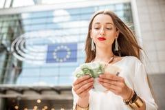 Donna con soldi vicino alla costruzione del Parlamento a Brussel Immagine Stock Libera da Diritti