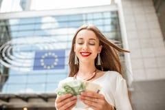 Donna con soldi vicino alla costruzione del Parlamento a Brussel Immagini Stock Libere da Diritti