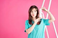 Donna con spruzzo cosmetico su fondo rosa Immagine Stock Libera da Diritti