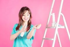 Donna con spruzzo cosmetico su fondo rosa Immagini Stock Libere da Diritti