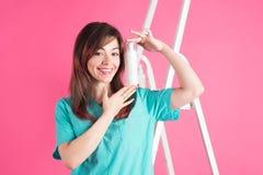 Donna con spruzzo cosmetico su fondo rosa Fotografia Stock
