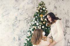 Donna con sua figlia che tiene una scatola con molto si di Natale Fotografie Stock Libere da Diritti