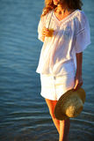 Donna con succo d'arancia e un cappello di paglia a disposizione sulla spiaggia Fotografia Stock
