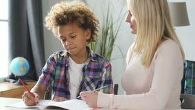 Donna con suo figlio abile preparare compito per scuola archivi video