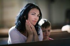 Donna con suo pregare del figlio Immagine Stock