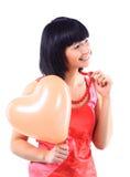 Donna con un aerostato heart-shaped Immagine Stock