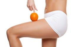 Donna con un'arancia che mostra una pelle perfetta Fotografia Stock