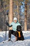 Donna con un cane sul camminare in legno di inverno fotografia stock libera da diritti