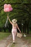 Donna con un canestro di vimini, un cappello, gli impulsi rosa ed i fiori camminante su una strada campestre immagine stock