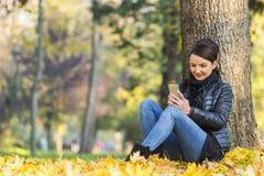 Donna con un cellulare in una foresta in autunno Immagini Stock Libere da Diritti