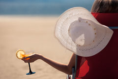 Donna con un cocktail di frutta su una spiaggia tropicale Fotografie Stock