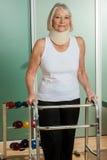 Donna con un collo ortopedico facendo uso del camminatore fotografie stock libere da diritti