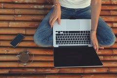 Donna con un computer portatile che si siede sul pavimento di bambù Fotografia Stock