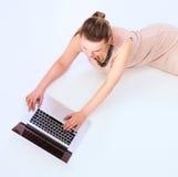 Donna con un computer portatile che si trova sul pavimento Fotografia Stock