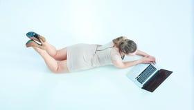 Donna con un computer portatile che si trova sul pavimento Immagini Stock Libere da Diritti
