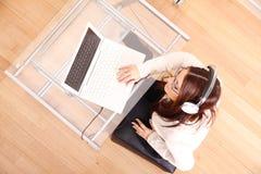 Donna con un computer portatile e le cuffie Immagini Stock Libere da Diritti